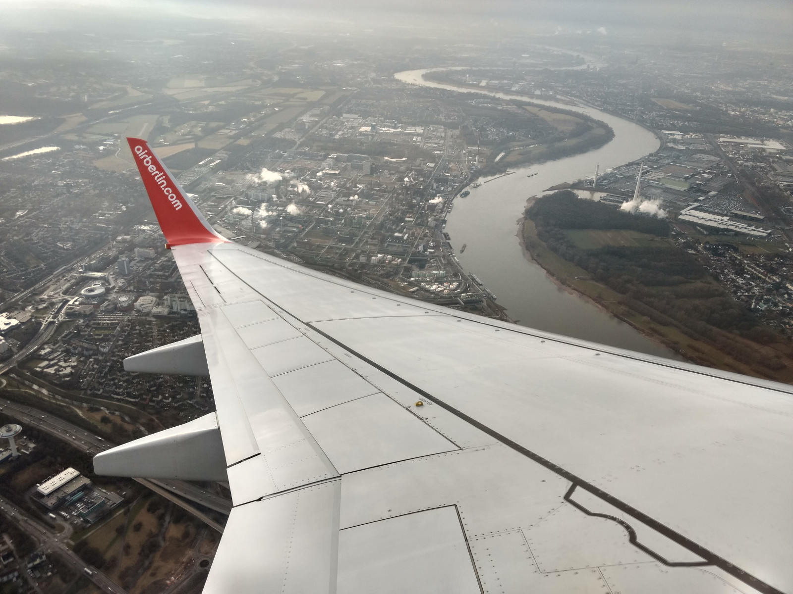 A photo of cologne out of an airplane with the wing of the plane