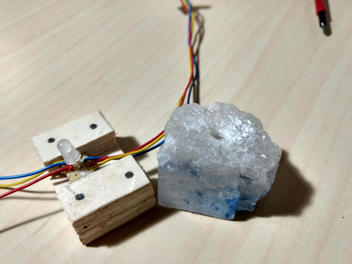 Ein einzelner Salzkristall neben seinem Holzsockel